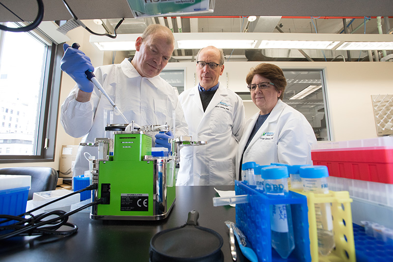 Marty Timour, research technician, Genomics Core; Peter Linsley, PhD; and Vivian Gersuk, PhD; observe the Mantis robot, which makes single cell analysis fast, accurate and efficient. Generous donor contributions recently funded the new equipment.