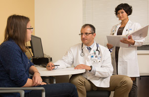 Doctor and clinical research assistant meeting with patient