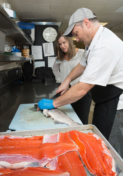 Marc Allen of Food and Nutrition Services prepares salmon to be served in the Virginia Mason Hospital cafeteria. Mary Howard, director, Food and Nutrition Services, watches.