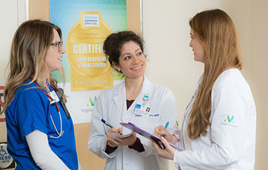 Photo: Three women discussing a patient transfer.