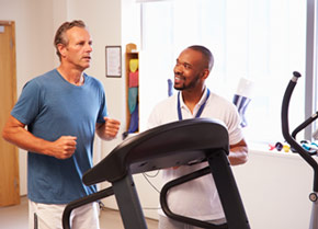 Man running on a treadmill next to a doctor.